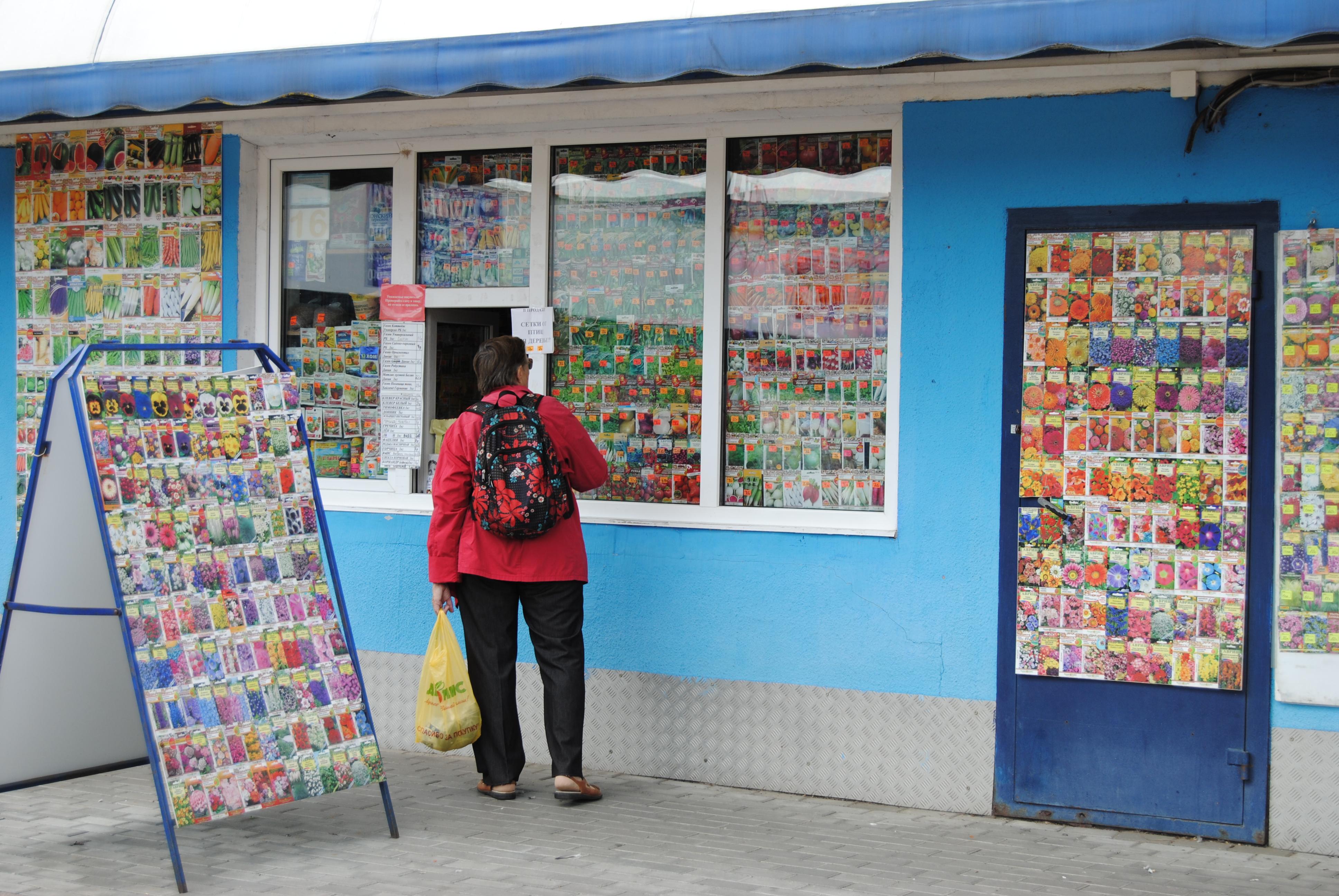 Una mujer compra semillas de flores en el mercado Komarovskiy de Minsk